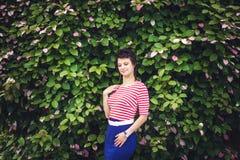 Portret van een aantrekkelijke jonge sensuele vrouw op een achtergrond van klimopmuur met groene bladeren Stock Foto's