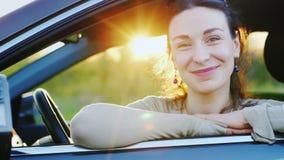 Portret van een aantrekkelijke jonge vrouw in de auto Glimlachen, die de camera door het open venster, na zonsondergang bekijken stock video