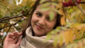 Portret van een aantrekkelijke Kaukasische vrouw die tegen een achtergrond van de herfstgebladerte glimlachen Royalty-vrije Stock Fotografie