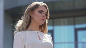 Portret van een aantrekkelijke onderneemster tegen de achtergrond van een commercieel centrum stock videobeelden