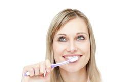 Portret van een aantrekkelijke vrouw die haar tanden borstelt Stock Foto's