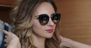 Portret van een aantrekkelijke vrouw met krullen in zonnebril stock video