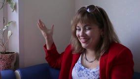 Portret van een aantrekkelijke vrouw op middelbare leeftijd in rode kleren Zij spreekt enthousiast, lacht en glimlacht stock videobeelden