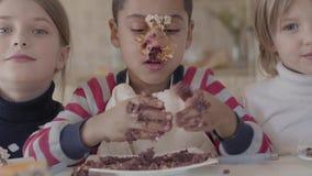 Portret van een Afrikaans-Amerikaanse die jongen in een cake wordt bevuild en het kneden van een stuk die van cake in een plaat o stock footage