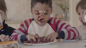 Portret van een Afrikaans-Amerikaanse die jongen in een cake wordt bevuild en het kneden van een stuk die van cake in een plaat o stock videobeelden