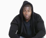 Portret van een in Afrikaanse Amerikaanse mens die sweatshirt met een kap over grijze achtergrond dragen Stock Foto's