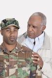 Portret van een Afrikaanse Amerikaanse militair van de V.S. Marine Corps met vader over grijze achtergrond stock afbeeldingen