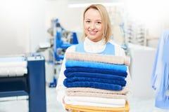 Portret van een arbeider die van de meisjeswasserij een schone handdoek houden royalty-vrije stock foto's