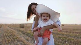 Portret van een baby in een grote hoed die op het gebied met haar moeder in de zonsondergang lopen Gelukkige jonge vrouw met klei stock footage