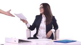Portret van een bedrijfsvrouw Het brunette in in bureau zitten en documenten ondertekenen en glazen die geeft hen aan glimlachen stock video