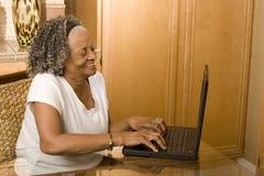 Portret van een bejaarde Afrikaanse Amerikaanse vrouw op haar computer stock afbeeldingen