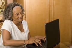 Portret van een bejaarde Afrikaanse Amerikaanse vrouw op haar computer stock afbeelding