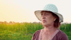 Portret van een bejaarde die in het platteland leven Een volwassen vrouw draagt een witte hoed genietend van de mening in stock footage