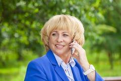 Portret van een bejaarde mooie vrouw die op een celtelefoon spreken Royalty-vrije Stock Foto's
