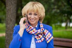 Portret van een bejaarde mooie vrouw die op een celtelefoon spreken Royalty-vrije Stock Afbeeldingen