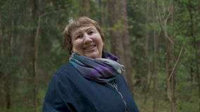 Portret van een bejaarde mooie vrouw Lopend in het park, in de avond, in de lente stock footage