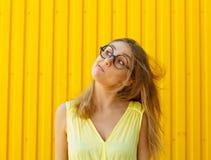 Portret van een blij meisje die stuk speelgoed grappige glazen dragen die wegblazen stock fotografie