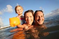 Portret van een blije familie die samen in het overzees zwemmen Stock Afbeeldingen