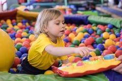 Portret van een blonde jongen in een gele t-shirt Het kind glimlacht en speelt in de speelkamer van de kinderen Balpool stock fotografie