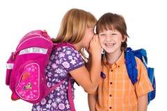 Portret van een blonde meisje dat in het oor van de jongen fluistert Stock Foto's