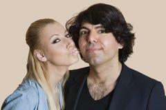 Portret van een blonde vrouw die met bestrooide lippen de jonge mens over gekleurde achtergrond kussen Royalty-vrije Stock Foto