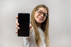 Portret van een blondemeisje met een smartphone in haar hand Slimme technologie Mobiele aansluting Smartphone van kinderen apps stock foto