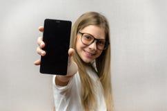 Portret van een blondemeisje met een smartphone in haar hand Slimme technologie Mobiele aansluting Smartphone van kinderen apps royalty-vrije stock afbeeldingen