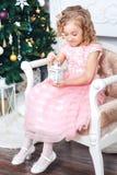 Portret van een blondemeisje in een roze kleding tegen de achtergrond van een Kerstboom met een witte kandelaar in de handen royalty-vrije stock foto's