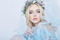 Portret van een blondevrouw met een kroon op haar hoofd en een blauwe gevoelige lichte transparante kleding Grote blauwe ogen en  stock foto's