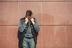 Portret van een boze jonge knappe kerel in een zwart vest op de straat stock fotografie