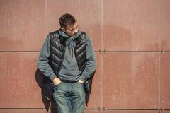 Portret van een boze jonge knappe kerel in een zwart vest op de straat royalty-vrije stock foto's