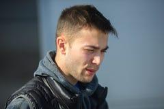 Portret van een boze jonge knappe kerel in een zwart vest op de straat royalty-vrije stock fotografie