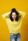 Portret van een boze jonge vrouw over gele studioachtergrond royalty-vrije stock afbeeldingen