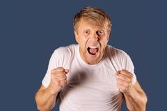 Portret van een boze mens in de witte vuisten van de t-shirtholding op blauwe achtergrond royalty-vrije stock afbeeldingen