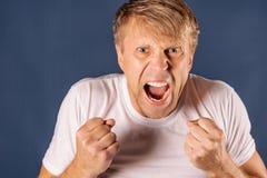 Portret van een boze mens in de witte vuisten van de t-shirtholding op blauwe achtergrond royalty-vrije stock fotografie