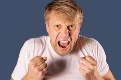 Portret van een boze mens in de witte vuisten van de t-shirtholding op blauwe achtergrond royalty-vrije stock afbeelding