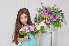 Portret van een brunete mooi meisje in een turkooise kleding met het vragen van blik royalty-vrije stock afbeelding