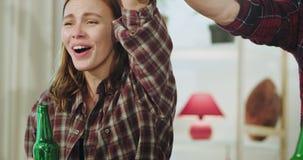 Portret van een charismatische roodharigedame met een grote glimlach zij die een overwinning van haar beste voetbalteam vieren in stock video