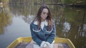 Portret van een charmante jonge vrouw in zonnebril en een denimjasje die op een boot op een meer of een rivier drijven Mooi stock videobeelden