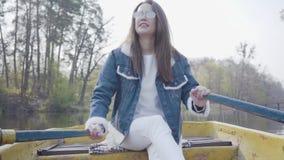 Portret van een charmante leuke vrouw in glazen en een denimjasje die op een boot op een meer of een rivier drijven Mooi stock video