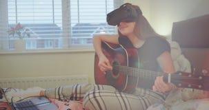 Portret van een dame die op een gitaar spelen en haar virtuele werkelijkheidsglazen gebruiken, zij die nieuwe technologie gebruik stock videobeelden