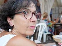 Portret van een donkerbruine vrouw op middelbare leeftijd met oogglazen, outdoo stock afbeelding