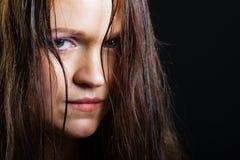 Portret van een droevig jong meisje met lang nat haar op een zwarte Royalty-vrije Stock Afbeelding