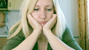 Portret van een droevige en bored jonge blonde vrouwenzitting in keuken, droefheids en depressieconcept stock videobeelden