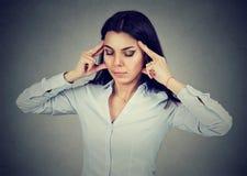 Portret van een droevige jonge vrouw met ongerust gemaakte beklemtoonde gezichtsuitdrukking die hoofdpijn hebben stock foto's