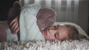Portret van een droevige tiener en een teddybeer die in bed liggen stock footage