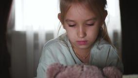 Portret van een droevige tiener en een teddybeer die in bed liggen stock videobeelden