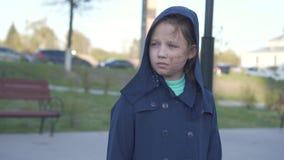 Portret van een droevige tiener met een gebrand gezicht die onderaan de straat met een kap op de achtergrond van cityscape lopen stock videobeelden