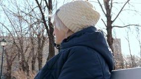 Portret van een eenzame gedeprimeerde bejaarde hogere vrouwenzitting op een bank in stadspark in de vroege lente in zonnige dag - stock footage