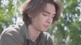 Portret van een eenzame gedeprimeerde droevige jonge mens met het doordringen in zijn neus en steunen die in het park zitten De k stock footage